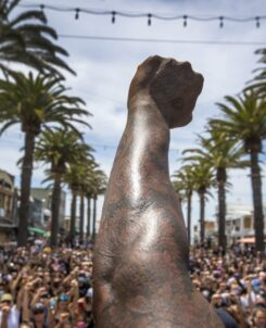 An arm raised into a fist in front of a crowd of people whose fists are raised as well