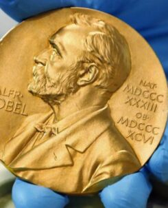 A hand holding a gold coin of the Nobel Peace Prize