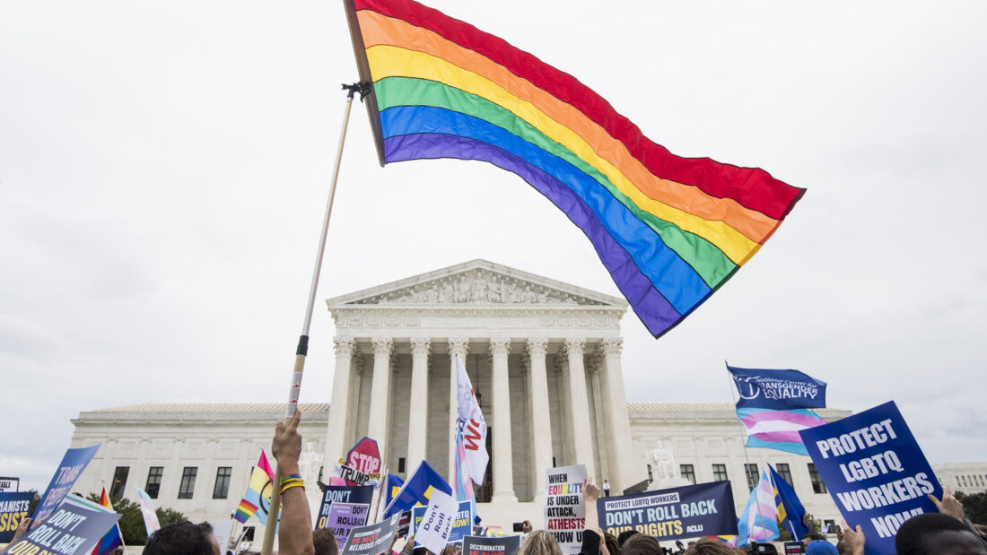 Pride rally taking place outside the Supreme Court Building with a person waving a pride flag