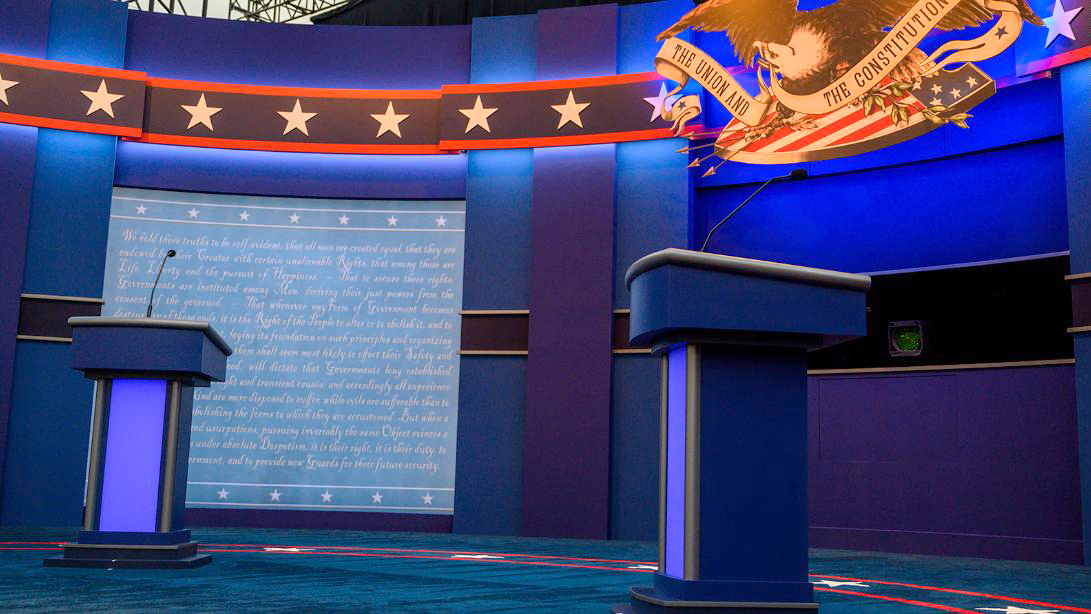 empty debate stage with podiums on either side of the picture, with a screen behind one of the podiums.