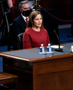 Justice Amy Coney Barrett sitting behind a desk at her Senate hearing for the nomination of Supreme Court Justice