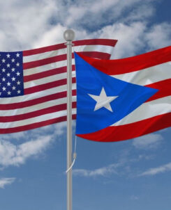 Picture of a U.S. and Puerto Rican flag side by side with the sky as the background