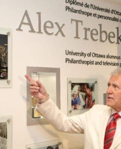 Alex Trebek pointing to a picture of himself