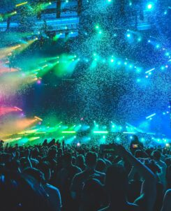 People at a concert with colorful lights over the crowd