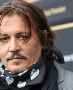 photo of johnny depp with a mask around his neck looking at the camera