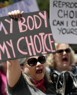 """Women in a pro-choice rally holding signs, one of which says """"my body my choice"""""""