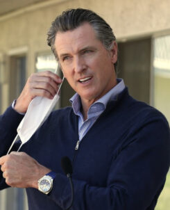 Photo of Governor Newsom holding a mask with two hands outside a building