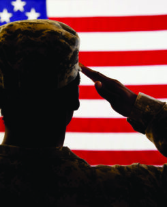 image of a soldier facing backwards saluting the american flag in the background