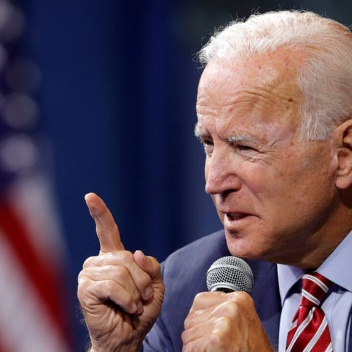 Image of Joe Biden looking to the left holding a microphone with one hand and the other raising a finger