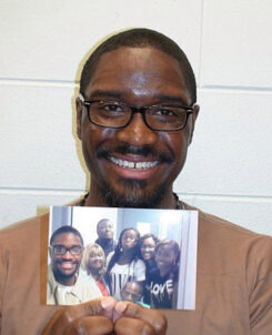 A man, Brandon Bernard, holding a picture of him and several others.