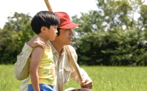 a young boy with his father kneeling next to him, his father has on a red baseball cap and is holding a bat