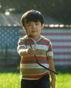 Promotional Image for Minari with a young boy in the forefront and an american flag on a wall behind him