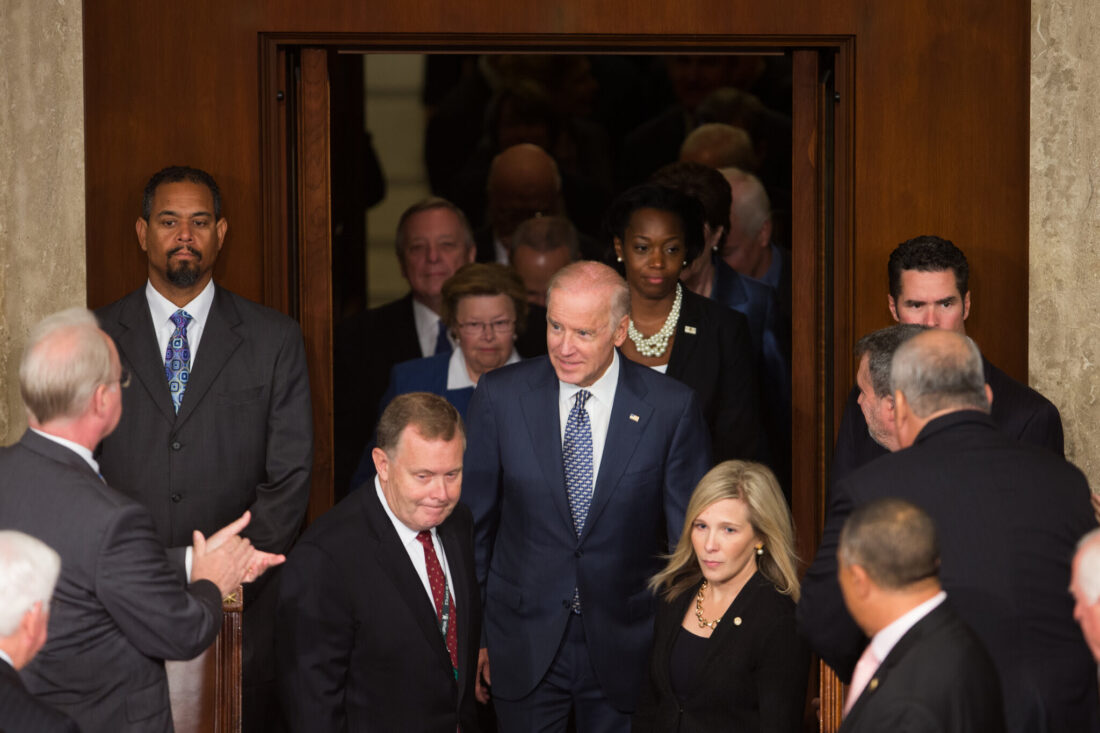 Biden going through a set of doors inside the Capitol Building with a crowd of people surrounding him
