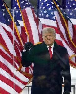 Trump standing with his fist raised with american flags behind him