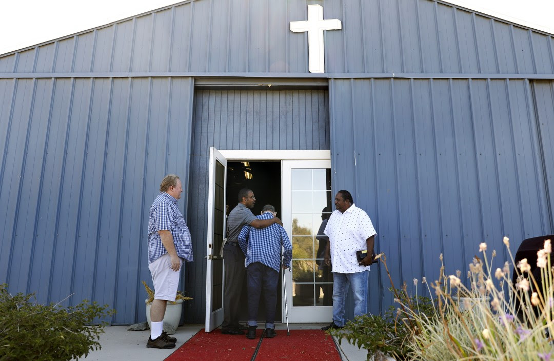 Photo of a church with an open door and two people going inside while another two linger on the outside