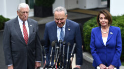 Photo of the top three democrats in congress: steny hoyer, chuck schumer, and nancy pelosi standing in front of a podium
