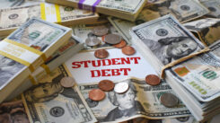 The words student debt written on paper in the middle of the photo surrounded by cash and coins