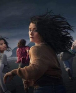 Image of a group of girls running along the shore in a dark setting with three of them looking back at the camera