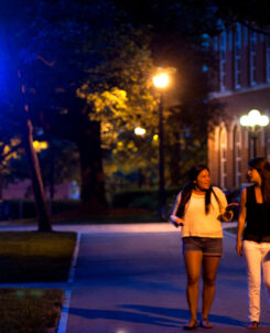 Two people walking on college campus at night.