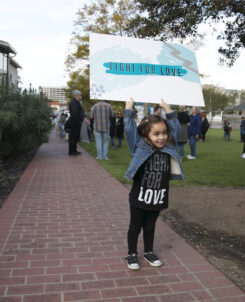 """a young girl holds a sign saying """"fight for love"""" at a love whittier event"""